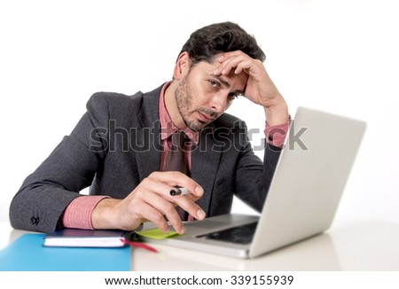 young attractive businessman in suit and tie sitting at office desk working on computer laptop looking tired and busy in work stress and overwork concept - stock photo