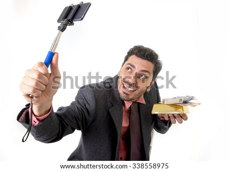 young attractive businessman in suit and tie taking selfie photo with mobile phone camera and stick posing happy and successful with gold bar and money  isolated on white background - stock photo