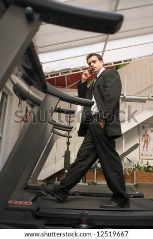 Young, attractive businessman on a treadmill while talking on his cell phone - stock photo