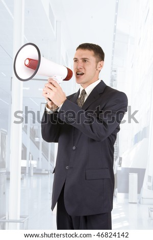 Young attractive businessman shouting into a megaphone - stock photo