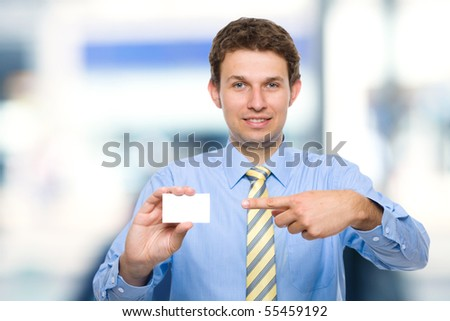 young attractive businessman shows his business card, blurred office background - stock photo