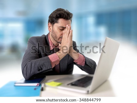 young attractive businessman sitting at office desk working on computer laptop covering his face desperate and worried in work stress and business problems concept - stock photo