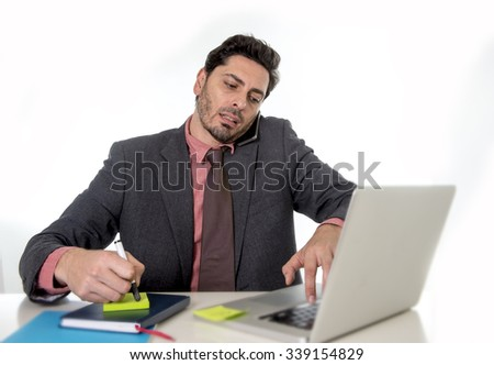 young attractive businessman sitting at office desk working on computer laptop looking active and busy writing note talking on mobile phone and typing on laptop in multitask concept - stock photo