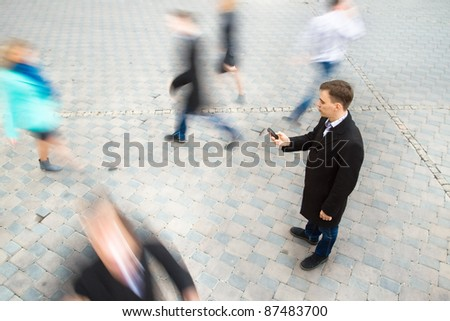 Young attractive businessman talking on mobile phone. Motion blurred commuters walking to work - stock photo
