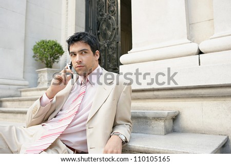 Young attractive businessman using a cell phone while sitting down on stone steps in a classic building, outdoors. - stock photo