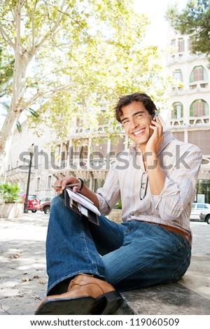 Young attractive businessman using a hands free device to make a call on his cell phone while sitting on a bench in a city square with classic architecture, smiling. - stock photo