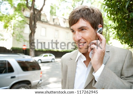 Young attractive businessman using an ear phone device to speak on his cell phone while standing in a classic city street, outdoors. - stock photo