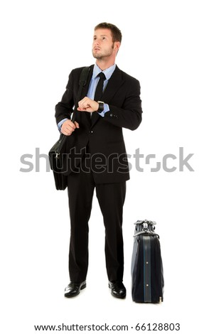 Young attractive businessman with briefcase and suitcase impatient checking the time. Looking forward to go. Studio shot. White background. - stock photo