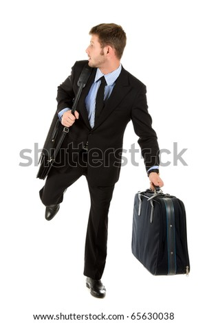 Young attractive businessman with briefcase and suitcase ready for travelling, Runs looking back. Studio shot. White background.