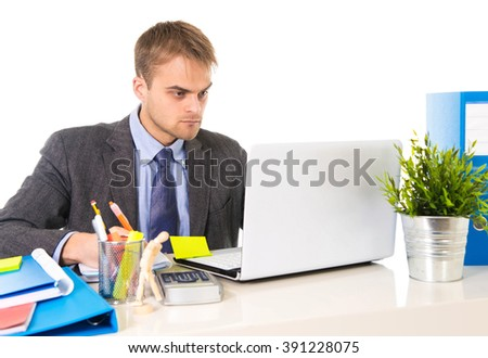 young attractive businessman working busy with laptop computer writing on pad with pen at office desk in business project success concept isolated on white background - stock photo