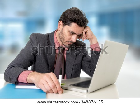 young attractive businessman working on computer laptop at office looking at the monitor concentrated in work stress and business concept - stock photo