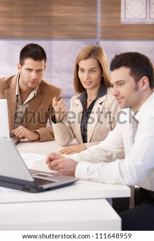Young attractive businesspeople working together using laptop, sitting at meeting table