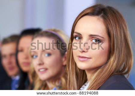 Young attractive businesswoman and her team in background - stock photo