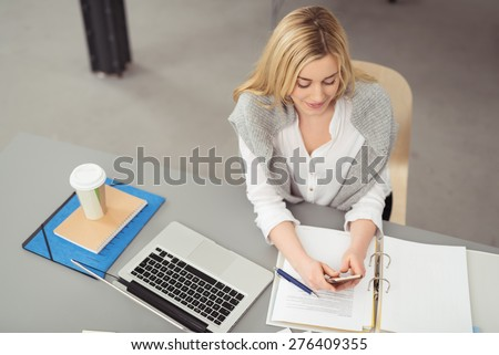 Young attractive businesswoman checking a call on her mobile phone as she sits working at her desk in the office, view from above - stock photo