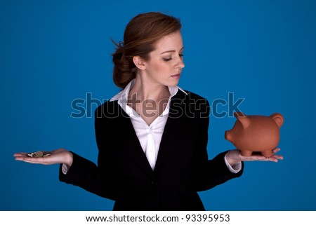 Young attractive businesswoman holding a piggybank and pound coins on a blue background. Young attractive Businesswoman. - stock photo