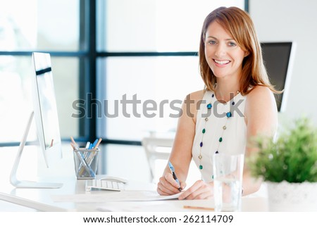 Young attractive businesswoman in office - stock photo