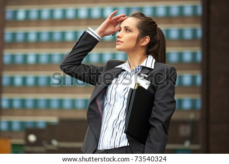 young attractive businesswoman in shirt and suit looks up, office building as background