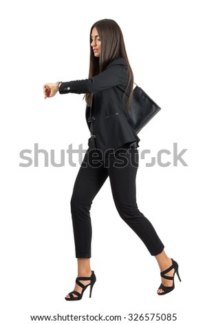Young attractive businesswoman in suit running while checking time on her watch.  Full body length portrait isolated over white studio background.  - stock photo