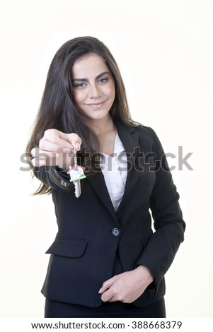 Young attractive businesswoman is offering us a house key against isolated white background. - stock photo