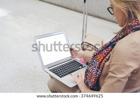 young attractive businesswoman is using laptop for work while waiting for a train at the railway station. Young girl sitting in front open net-book with copy space screen for your text or design.  - stock photo
