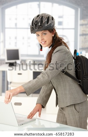 Young attractive businesswoman leaving office by bike, shutting down her laptop, wearing helmet and backpack.? - stock photo