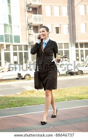young attractive businesswoman on the phone walking on street - stock photo