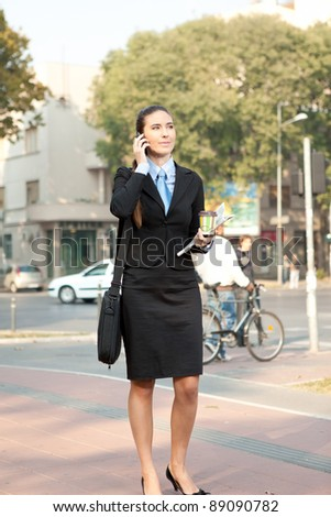 young attractive businesswoman on the phone walking on street, concept-city woman - stock photo