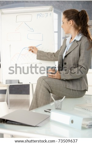 Young attractive businesswoman presenting in office, drawing diagram on whiteboard, sitting on desk. - stock photo