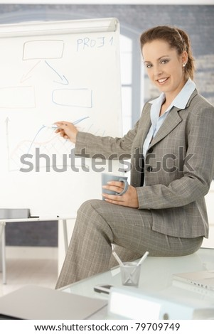 Young attractive businesswoman presenting in office, pointing, sitting on desk, smiling.? - stock photo
