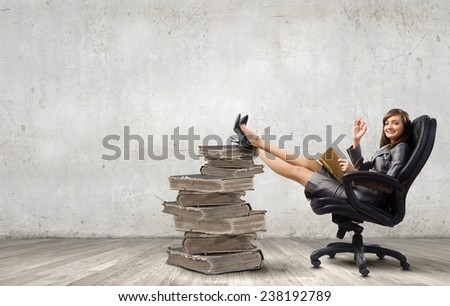 Young attractive businesswoman reading book in chair