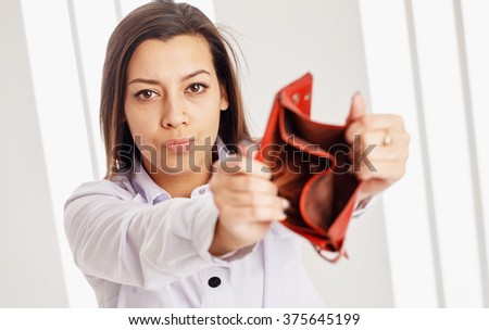Young attractive businesswoman showing an empty wallet to the camera. - stock photo