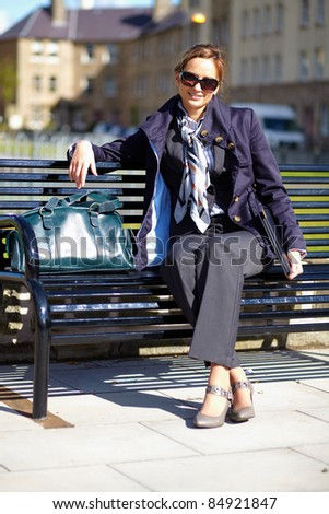 Young attractive businesswoman sits on bench with blurred buildings as background, street shoot