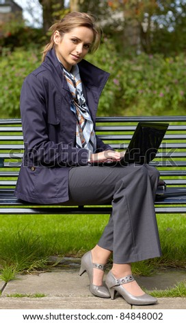 Young attractive businesswoman sits on park bench and work on her notebook