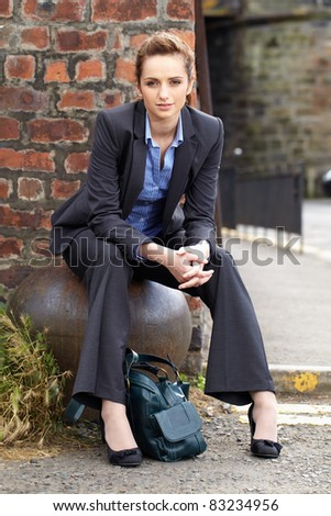 young attractive businesswoman sits on steel rusty ball, red brick wall as background - stock photo