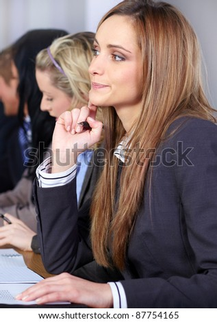 Young attractive businesswoman sitting at conference table with more people at background working on some paperwork - stock photo