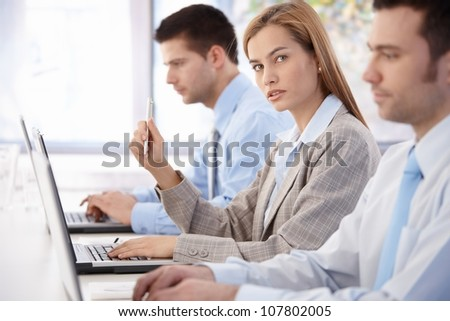 Young, attractive businesswoman sitting at meeting room, having business training. - stock photo
