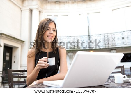 Young attractive businesswoman sitting in a luxurious coffee shop terrace with her laptop, holding a cup of coffee, smiling.