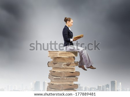 Young attractive businesswoman sitting on pile of old books reading