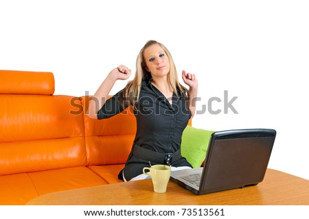 Young attractive businesswoman stretching her hands while sitting at her desk - stock photo