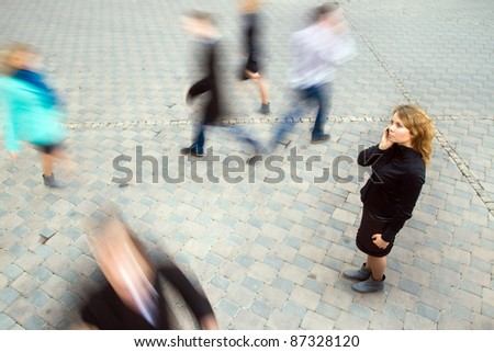 Young attractive businesswoman talking on mobile phone. Motion blurred commuters walking to work - stock photo