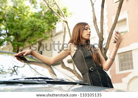 Young attractive businesswoman using a smart phone while leaning on a shiny car in a classic business street. - stock photo