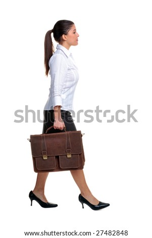 Young attractive businesswoman walking along carrying a brown leather briefcase, isolated on white background. - stock photo