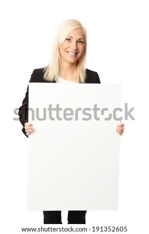 Young attractive businesswoman wearing a black jacket and white shirt, holding a large blank board. White background. - stock photo