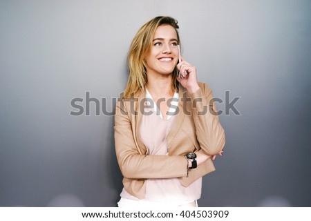 young attractive businesswoman with blonde hair posing on a gray background with copy space area for your text o design. Attractive student talking on smart-phone and smiling - stock photo