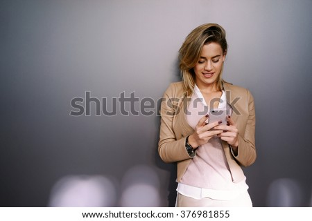young attractive businesswoman with blonde hair using smart-phone on a gray background with copy space area for your text o design. - stock photo