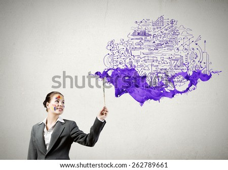 Young attractive businesswoman with paint brush and colorful business sketches - stock photo