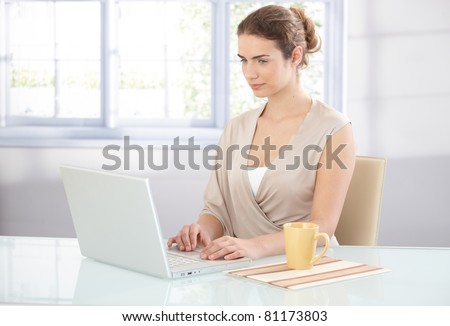 Young attractive businesswoman working in bright office, using laptop.? - stock photo