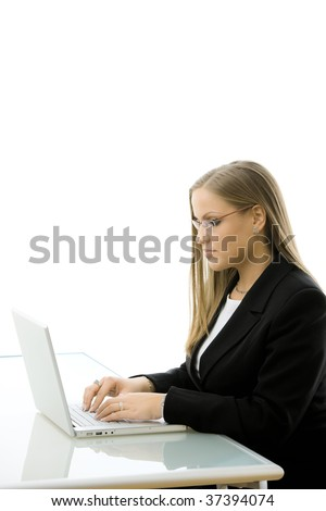 Young attractive businesswoman working on laptop computer at desk, sideview isolated on white background.