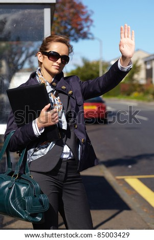 Young attractive busy businesswoman hailing taxi, outdoor shoot with blurred buildings and street as background