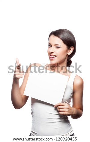 young attractive casual brunette caucasian female  girl holding blank white sign and  pointing at camera with index finger with funny expression on her face isolated on white - stock photo